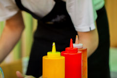 Man in black apron is preparing food with ketchup Royalty Free Stock Images