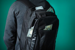 Man with a black backpack from which protrude dollars Royalty Free Stock Photography