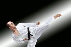 A man with a black belt strikes a high kick Royalty Free Stock Photo