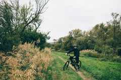 Man on black  bicycle. A cyclist on black bicycle travels through the countryside Royalty Free Stock Photography