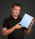 Man in black with blank box Stock Image