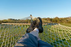 Man with black boots relaxing in a hammock, in a green field on a beautiful day stock photography