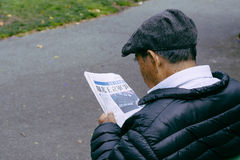 Man in Black Bubble Shell Jacket Reading Newspaper Beside Street Royalty Free Stock Photo