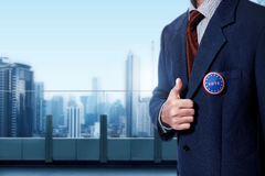 Man with black business suit with blue pinned button written 'VO Stock Photography