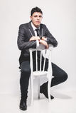 Man in black business suit on white chair at studio Stock Photos