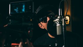 Man in Black Cap and Black Framed Sunglasses in Front Recording Microphone Stock Photography