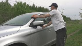 Man puts bucket on ground and starts washing automobile. Man in black cap comes to silver hatchback puts bucket on ground and starts washing automobile front stock video footage