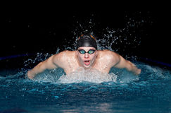 Man in black cap in swimming pool. Butterfly style Stock Images