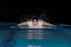 Man in black cap in swimming pool. Butterfly style Royalty Free Stock Photos