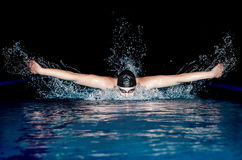Man in black cap in swimming pool. Butterfly style Stock Photography