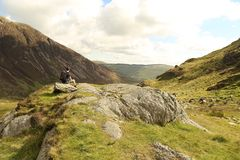 Man in Black Carrying Backpack Sitting on Rock With Overlooking Green Moutains Stock Image