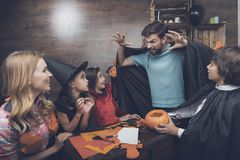 A man in a black cloak scares the children and the woman who are preparing the scenery for the Halloween party Royalty Free Stock Images