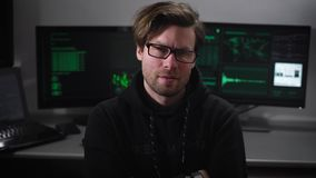 The man in the black close-up. Computer room. Young specialist for hacking computers in a black jacket with a stern look stock video footage