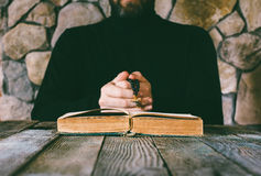 A man in black clothes with a prayer beads in hand praying in front of an old open book. The concept of praying, and studying. selective focus Stock Photos