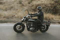 Man in black clothes riding a black classic american motorcycle. Riding a classic American motorcycle in a narrow road at sunrise royalty free stock photography