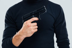 Man in black clothes standing and holding a gun Stock Photos