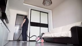 A man in black clothes vacuuming the floor. The man vacuums the floor of the house. The man is cleaning in the living room stock video