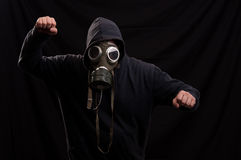 Man in black clothes wearing a classic gas mask over a dark back Royalty Free Stock Photos