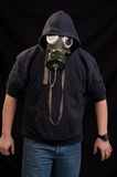 Man in black clothes wearing a classic gas mask over a dark back Royalty Free Stock Images