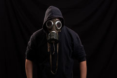 Man in black clothes wearing a classic gas mask over a dark back Stock Photo