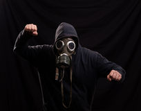 Man in black clothes wearing a classic gas mask over a dark back Royalty Free Stock Image