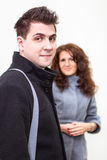 Man in black coat and girl behind on white background Royalty Free Stock Photos