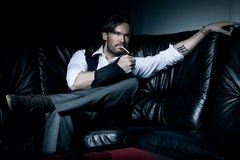 Man on the black couch Royalty Free Stock Image