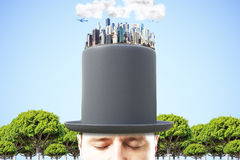 Man in black cylinder with 3D megapolis city on the top at blue Royalty Free Stock Image