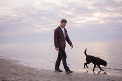 Man and black dog on the beach. Young caucasian male walking with dog on the morning beach, sunset on the sea or ocean and man with black labrador puppy Stock Photo