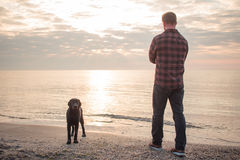 Man and black dog on the beach. Young caucasian male walking with dog on the morning beach, sunset on the sea or ocean and man with black labrador puppy Royalty Free Stock Images