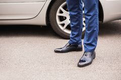 A man in black elegant shoes. Against the background of the car. Stylish clothes Royalty Free Stock Photo