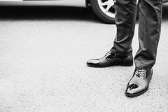 Black and white art monochrome photography. A man in black elegant shoes against the background of the car. Stylish clothes Stock Photo