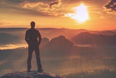 Man in black enjoy triumph. Hiker watch the borning of Sun. Just above the hilly horizon stock photo