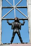 Man in black and fantastic design. Man in black leather cloth on background blue sky stand in wooden frame Stock Image