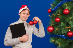 The man with the black folder costs near an elegant New Year tre Stock Images