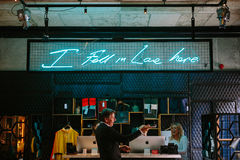 Man in Black Formal Suit Jacket Standing Near Girl and I Fall in Love Here Neon Signage Stock Image