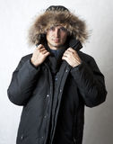 Man in black fur hood winter jacket. Fashion portrait of young handsome man in black fur hood winter jacket Royalty Free Stock Photography