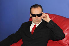 Man in black glasses sits on red sofa. Man in black glasses sits on red sofa and looks at camera Stock Photo