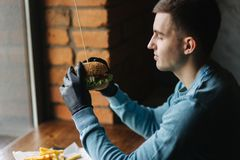 Man in black gloves takes a burger in his hands. Vegetarian burger with vegetables. Fresh healthy food.  stock image