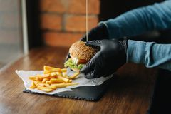 Man in black gloves takes a burger in his hands. Vegetarian burger with vegetables. Fresh healthy food.  royalty free stock photos