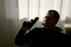 Man in black with gun. Man sitting by wondow in black jacket holding gun Stock Photos