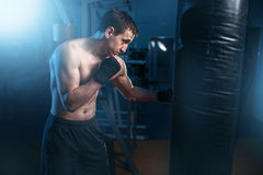 Man in black handwraps exercises with bag in gym Royalty Free Stock Images