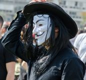 The man in black hat wearing white anonymous mask. At Purim event stock photography