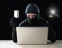 Man in black holding credit card and lock using computer laptop for criminal activity hacking bank account password Royalty Free Stock Photo