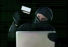 Man in black holding credit card using computer laptop for criminal activity hacking password and private information. Cracking password too access bank account Stock Photos