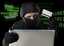 Man in black holding credit card using computer laptop for criminal activity hacking password and private information Royalty Free Stock Photos