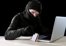 Man in black holding credit card using computer laptop for criminal activity hacking password and private information Stock Photo