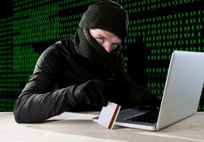 Man in black holding credit card using computer laptop for criminal activity hacking password and private information. Cracking password too access bank account Stock Image