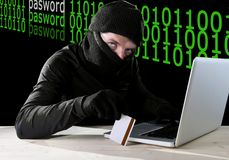 Man in black holding credit card using computer laptop for criminal activity hacking password and private information. Cracking password too access bank account Royalty Free Stock Image