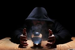 Man in a black hood with cristal ball. Summon evil stock photography